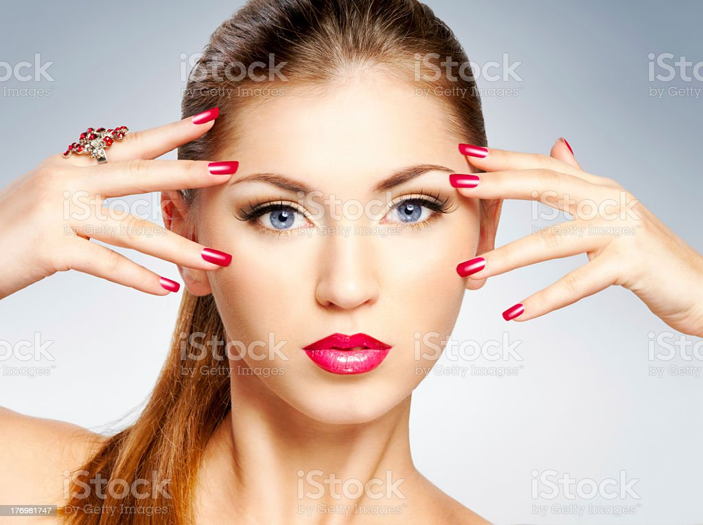 Woman's face with lipstick and painted nails royalty-free stock photo