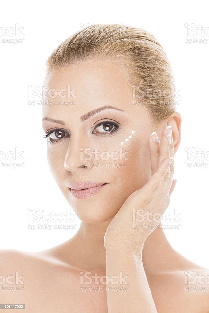 Woman's face with moisturizing cream under the eyes stock photo