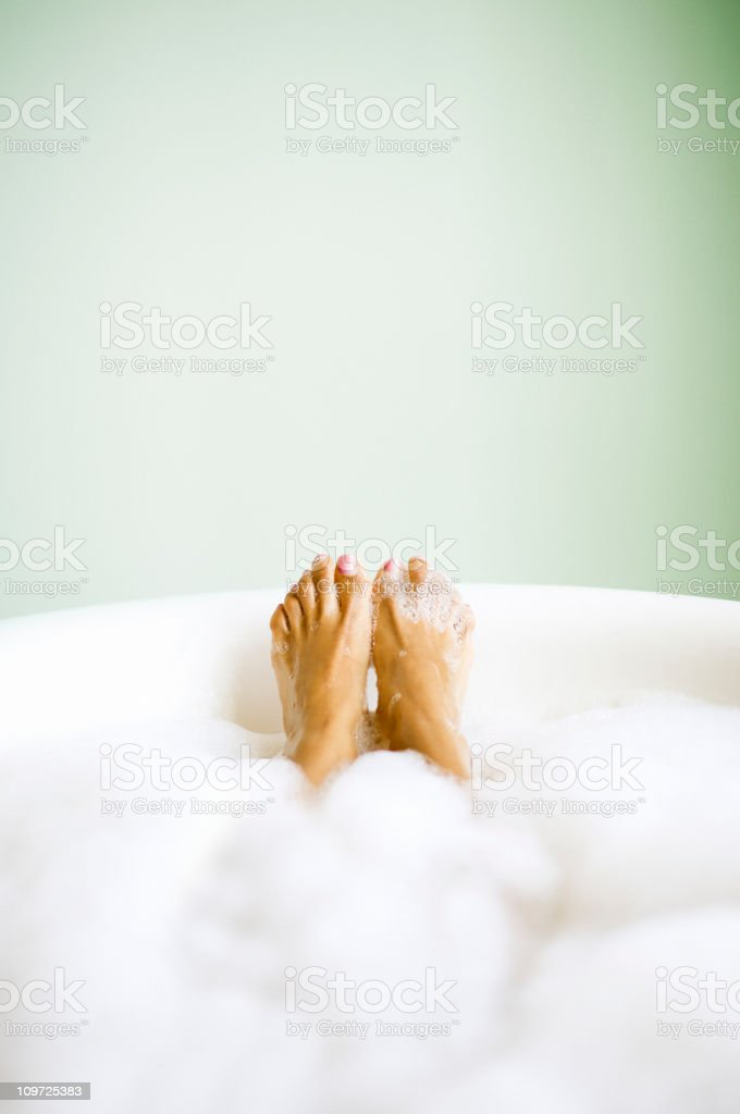 Woman's Feet Emerging in Bubble Bath stock photo