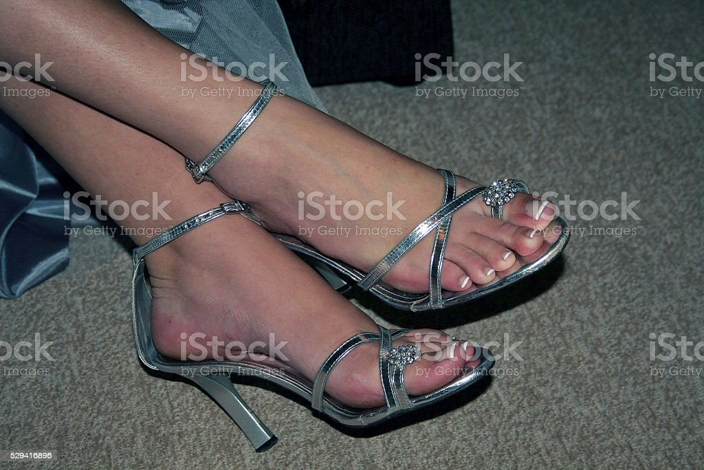 Woman's feet in silver shoes stock photo