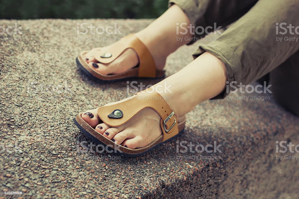 Woman's feet in yellow stylish summer sandals stock photo