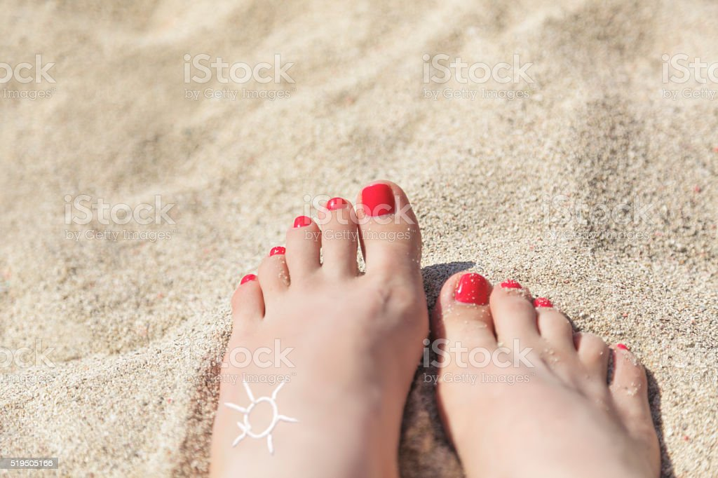 Woman's feet on a sandy beach in summer, close up stock photo