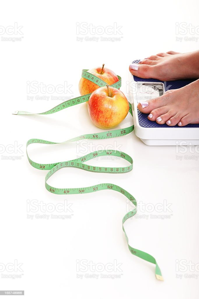 Woman's feet on weight scale with apples and tape measure royalty-free stock photo