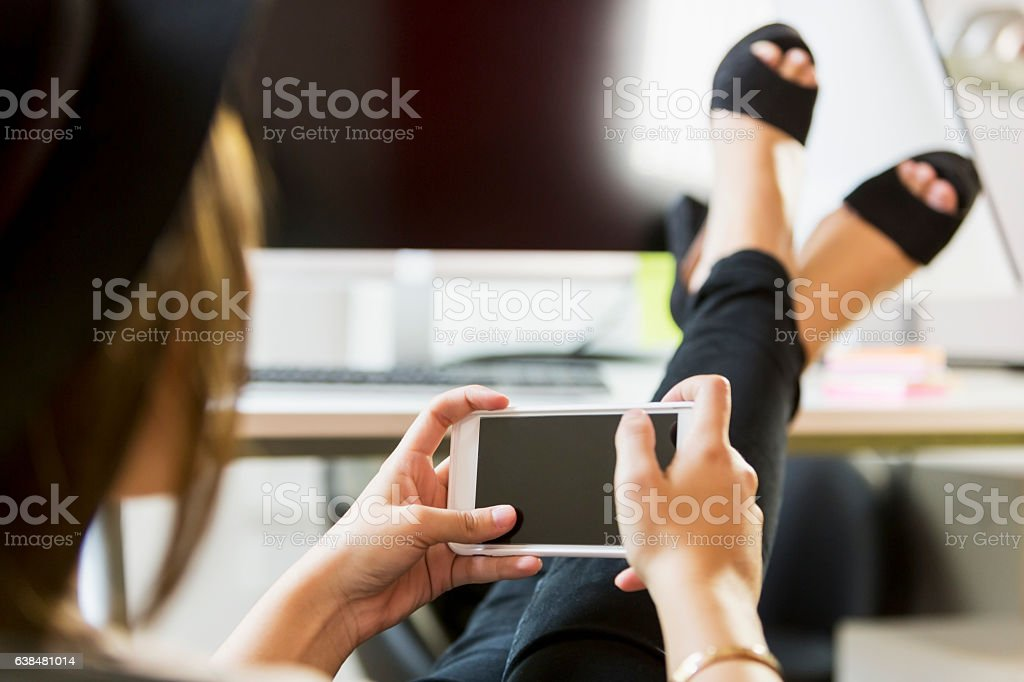 Womans feet propped up on desk, texting stock photo