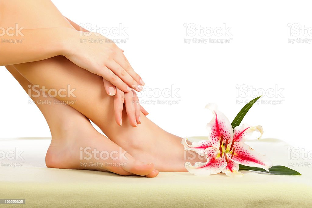 A woman's feet resting near a beautiful pink flower stock photo