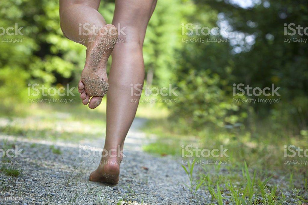 woman's feet running on gravel road stock photo