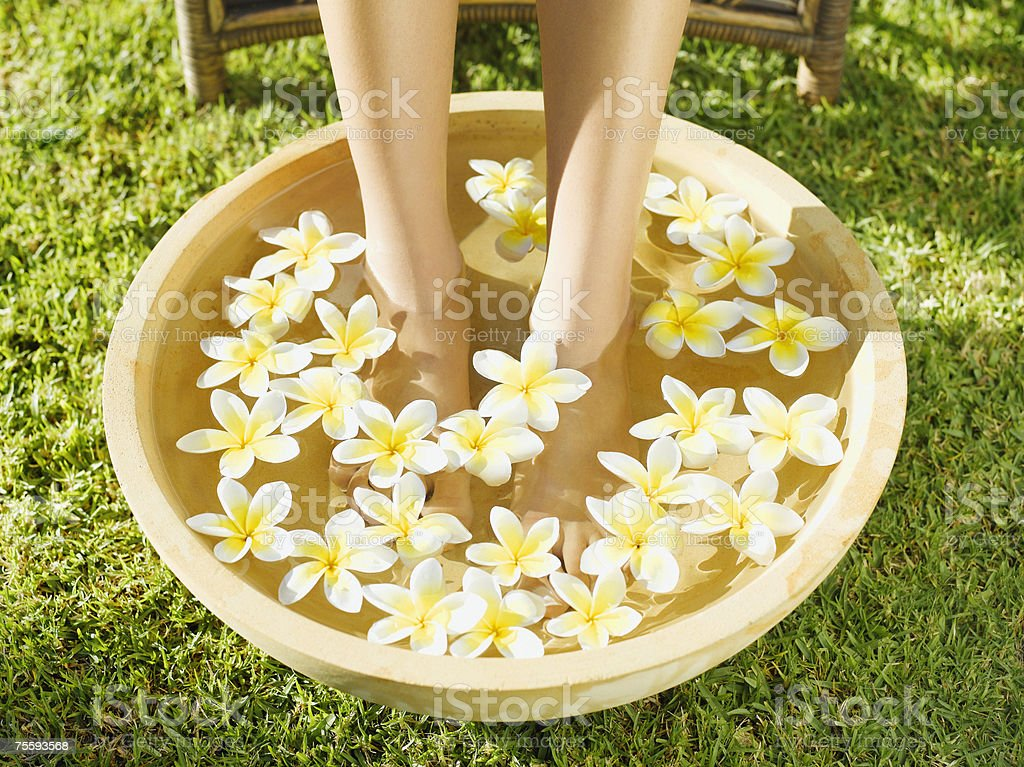 A woman's feet soaking in a bowl of water and flowers royalty-free stock photo