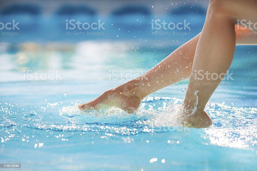 Woman's feet splashing the pool water stock photo