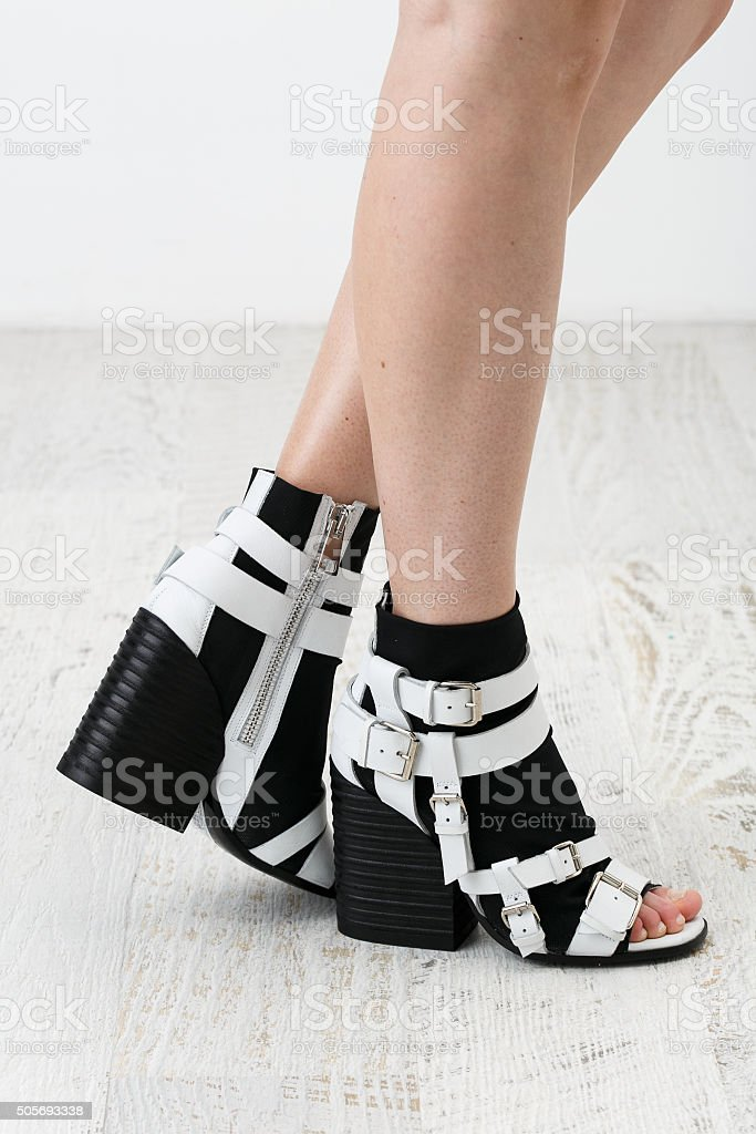 Woman's feets in the stylish black and white shoes stock photo
