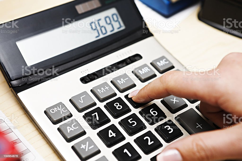 Woman's finger enters figures on electronic calculator stock photo