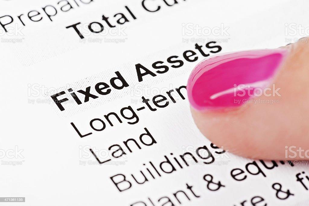 Woman's finger on balance sheet fixed assets stock photo