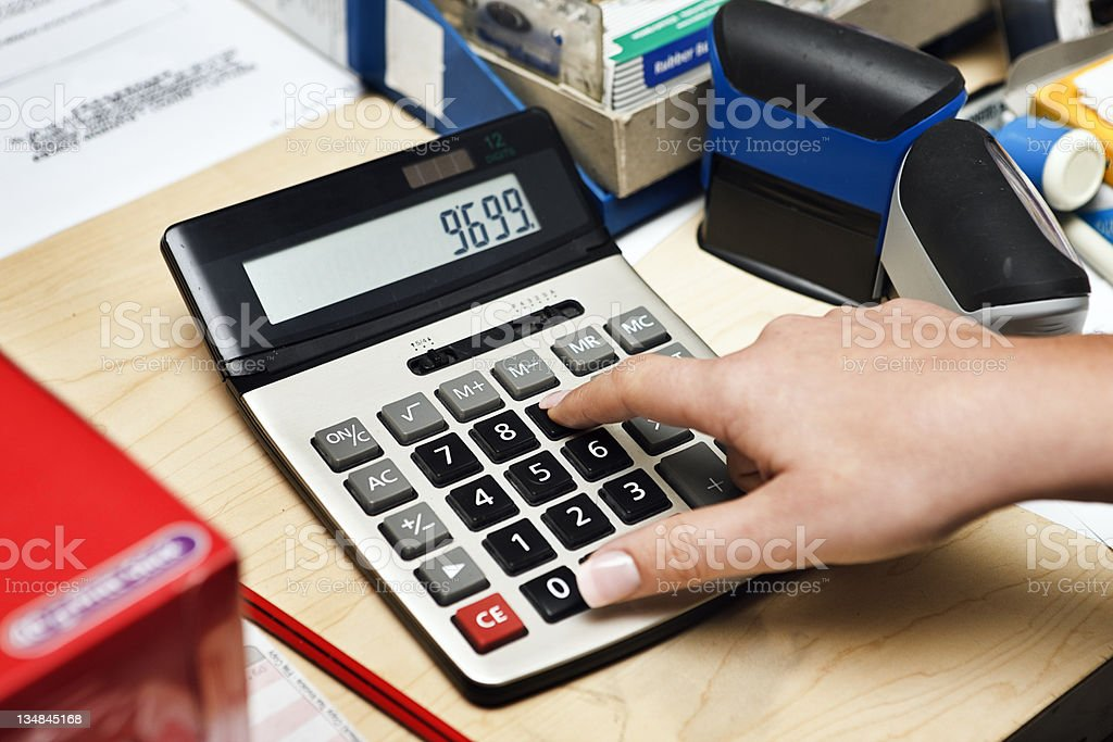 Woman's finger punches buttons on calculator stock photo