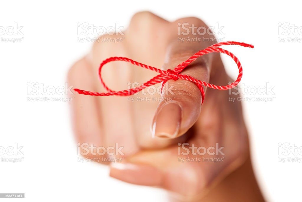 woman's finger tied with red thread stock photo