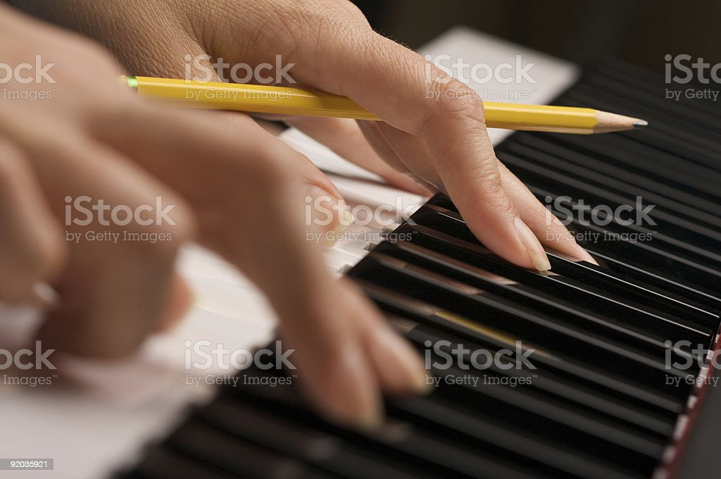 Woman's Fingers with Pencil on Piano Keys stock photo