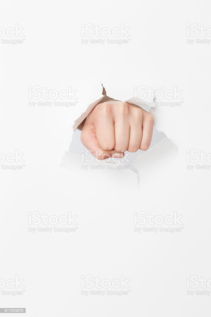 Woman's fist tearing though paper stock photo