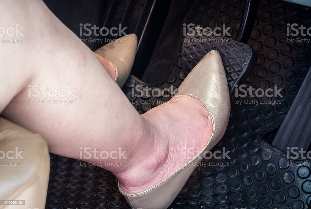 Woman's foot on the brake pedal of a car stock photo