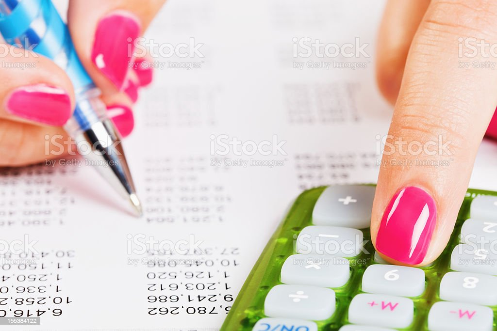 Woman's guide to finance: feminine hands check financial spreadsheet stock photo