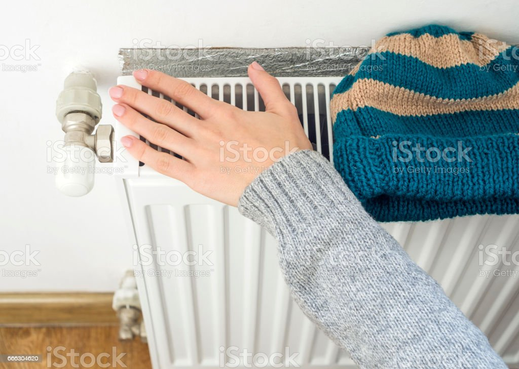 Woman's hand adjusting heater Thermostat in winter time stock photo