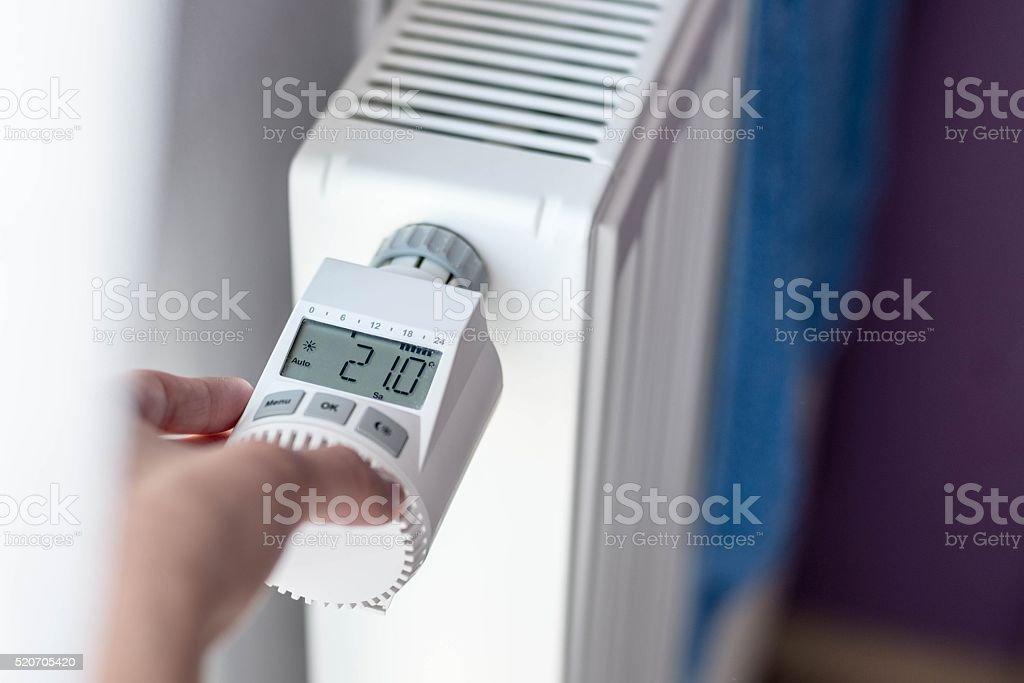 Woman's hand adjusting temperature stock photo