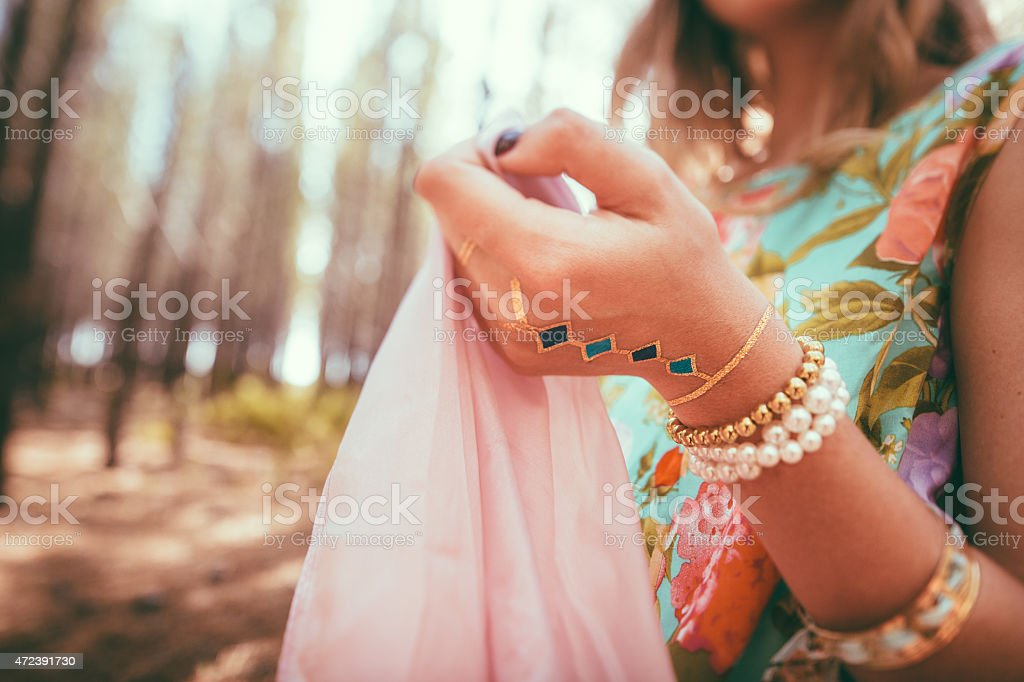 Woman's hand adorned with jewllery and a temporary tattoo stock photo