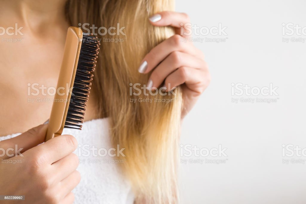 Woman's hand brushing blonde hair. Cares about a healthy and clean hair. Beauty salon. Empty place for a text on the gray background. stock photo