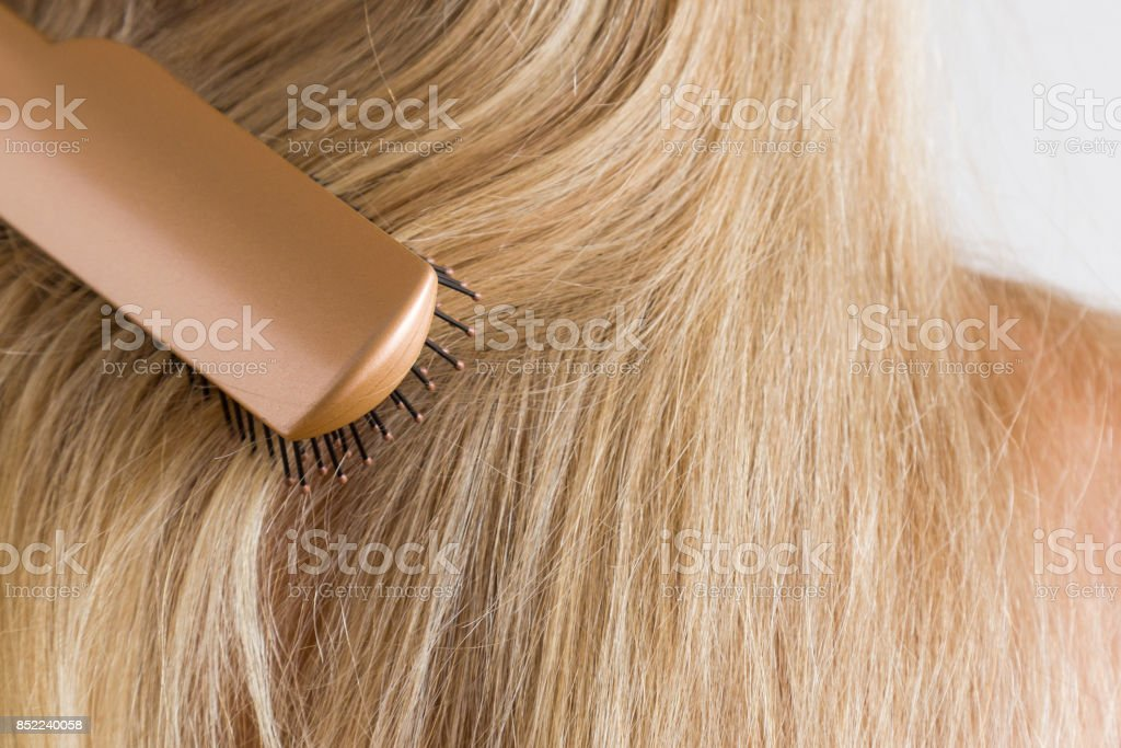 Woman's hand brushing blonde hair. Cares about a healthy and clean hair. Beauty salon. Close up. stock photo