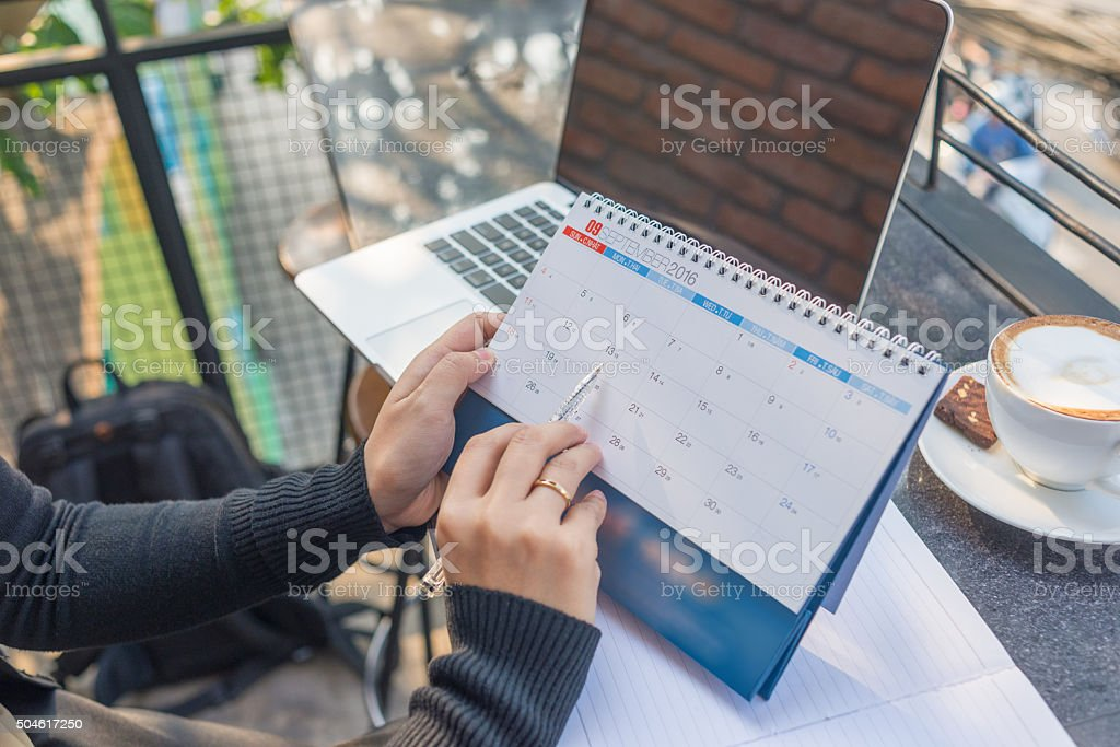 Woman's hand carrying calendar and pointing on it by pen stock photo