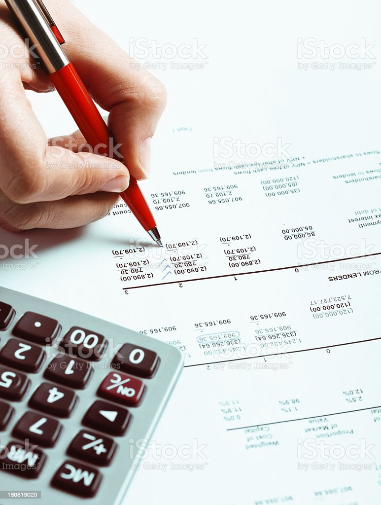 Woman's hand checking financial spreadsheet with calculator nearby stock photo