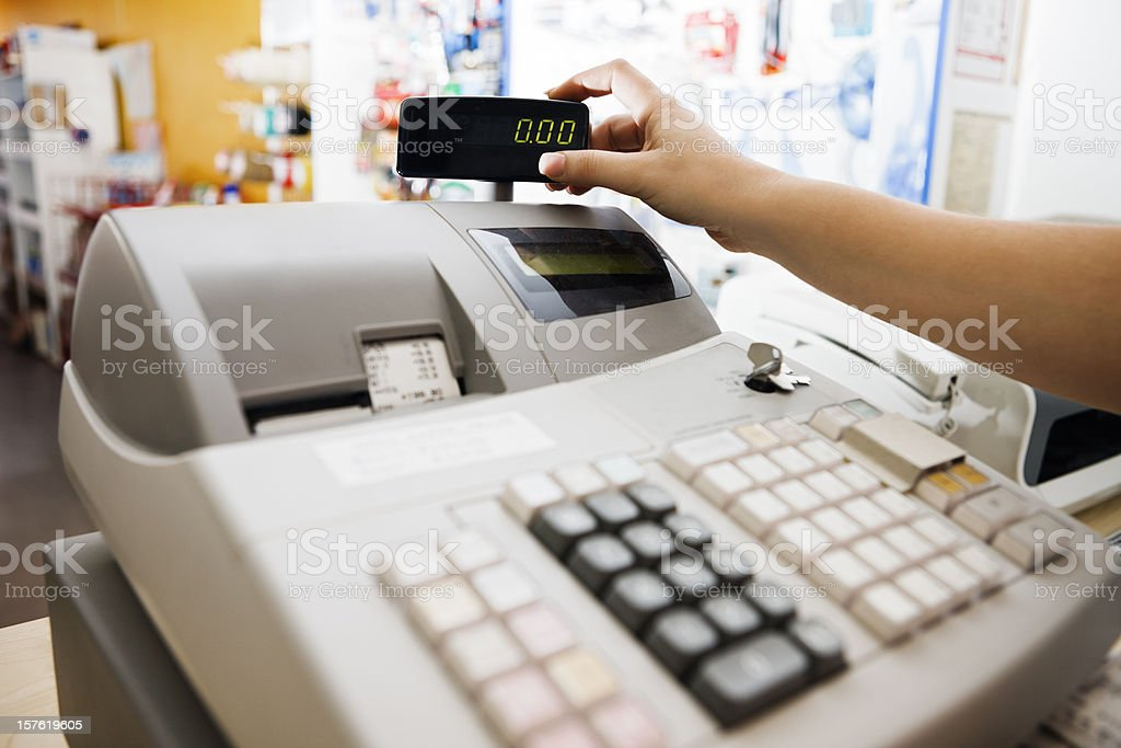 Woman's hand checks readout on cash register royalty-free stock photo