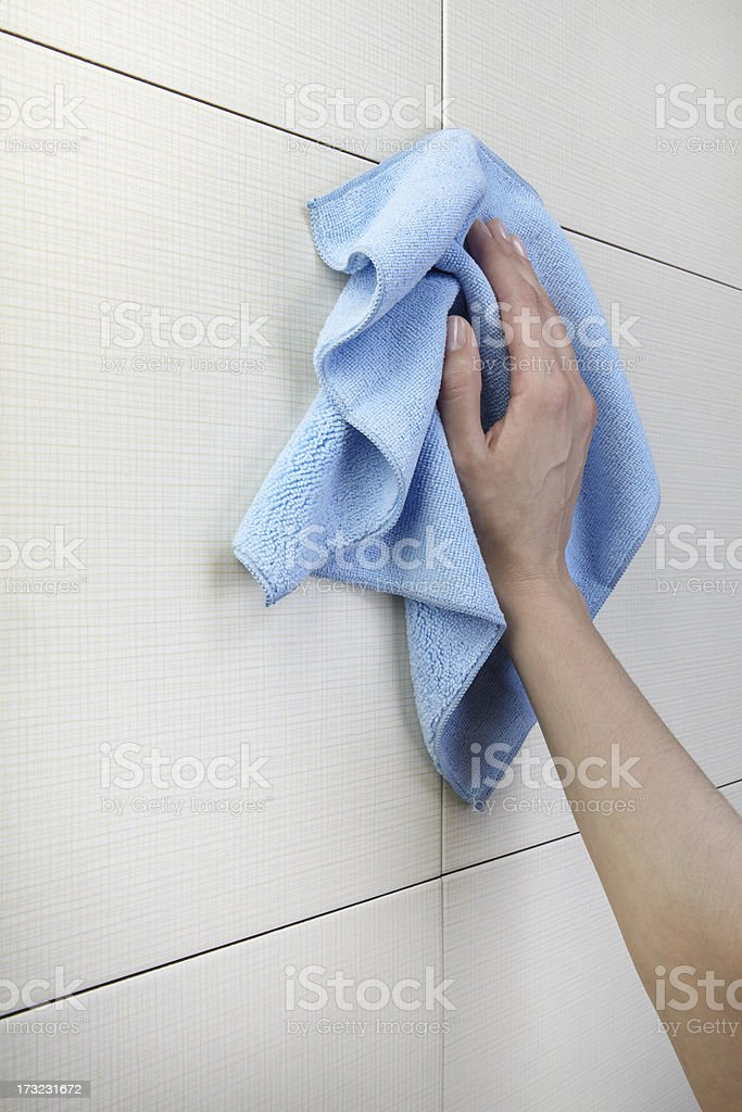 Woman's hand cleaning tile wall with blue rag royalty-free stock photo