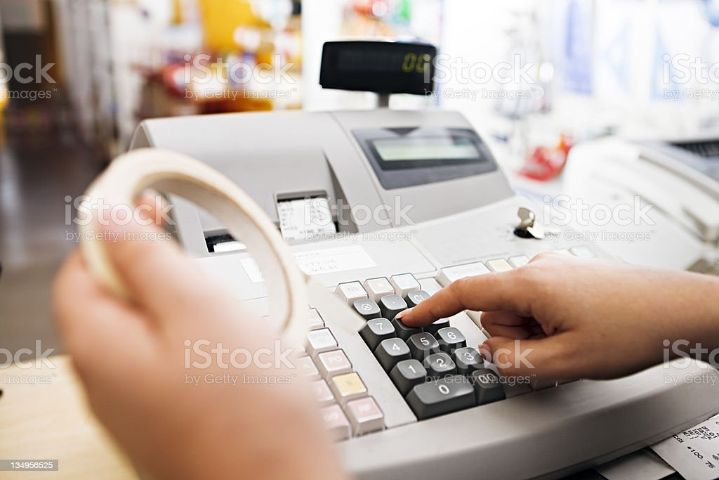 Woman's hand enters sale of tape on cash register stock photo