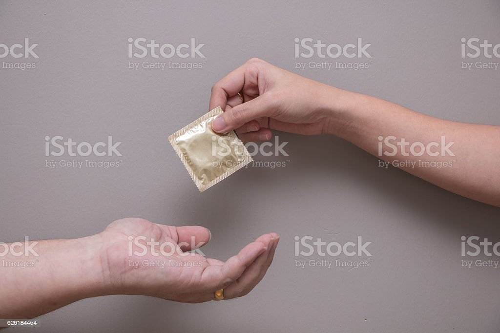 Woman's hand giving man's hand a gold condom stock photo
