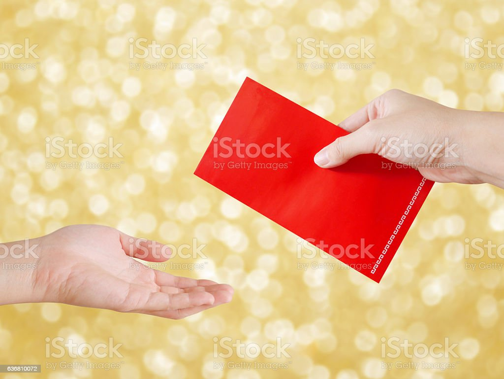 Woman's hand giving red packet on Chinese New Year stock photo