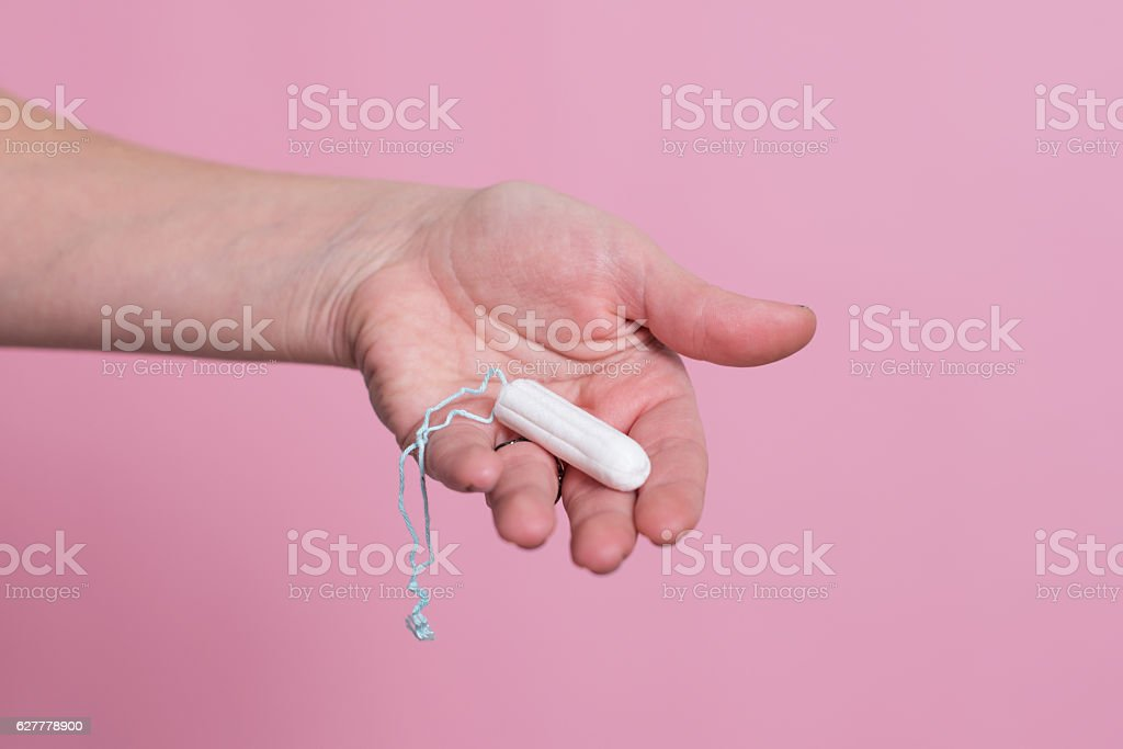 Woman's hand holding a clean cotton tampon stock photo