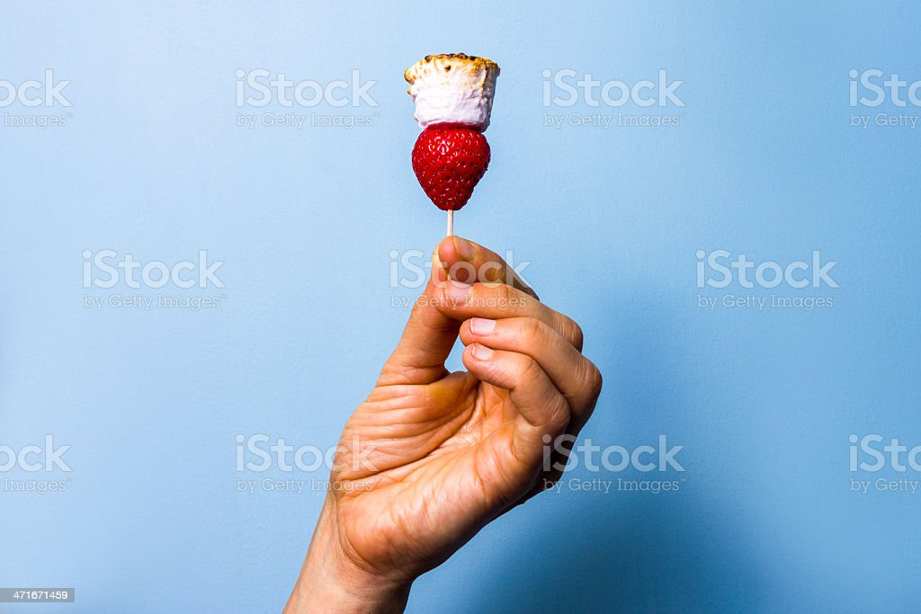 Woman's hand holding a toasted marshmallow and strawberry stock photo