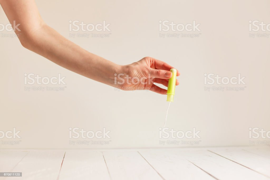 Woman's hand holding clean green cotton tampon. stock photo