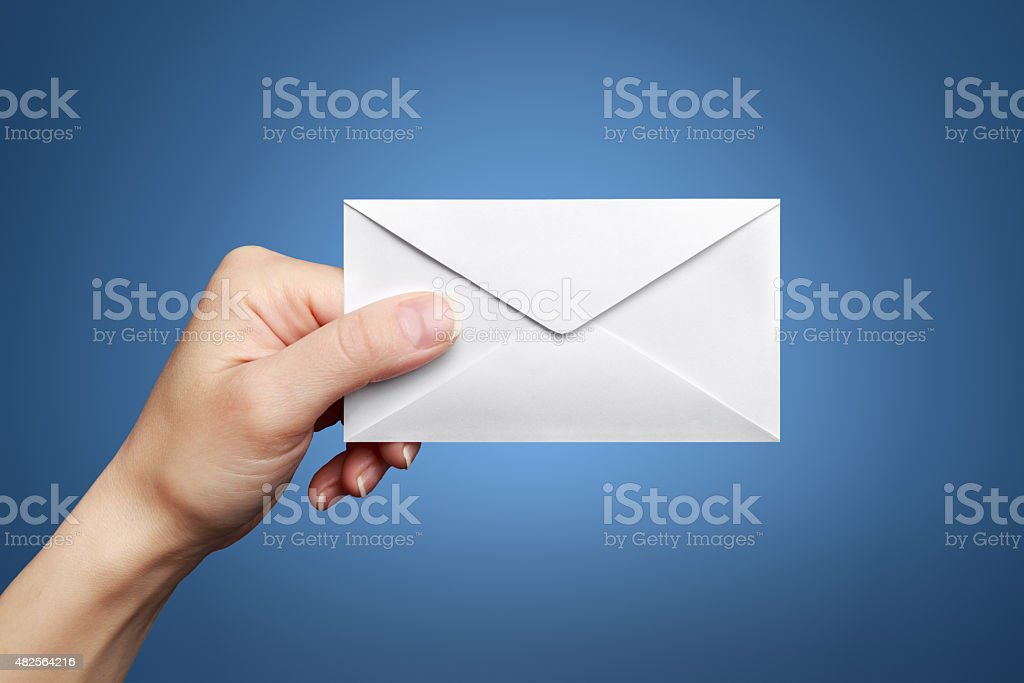 Woman's hand holding closed envelope stock photo