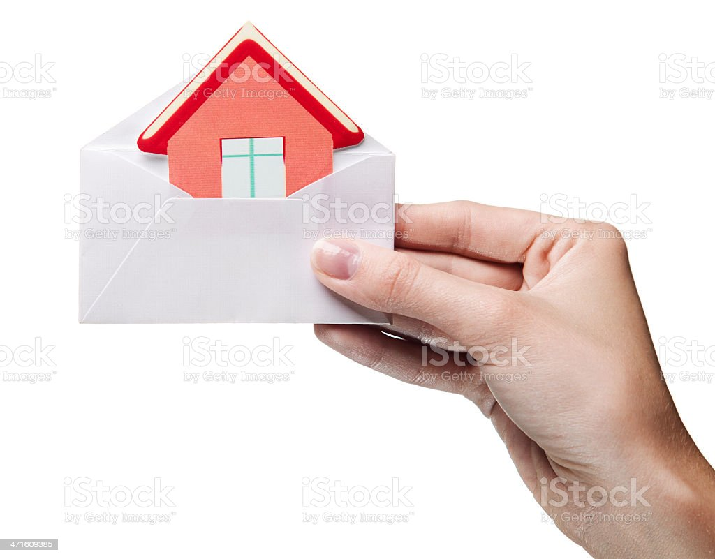 woman's hand holding envelope with a sign of the house royalty-free stock photo