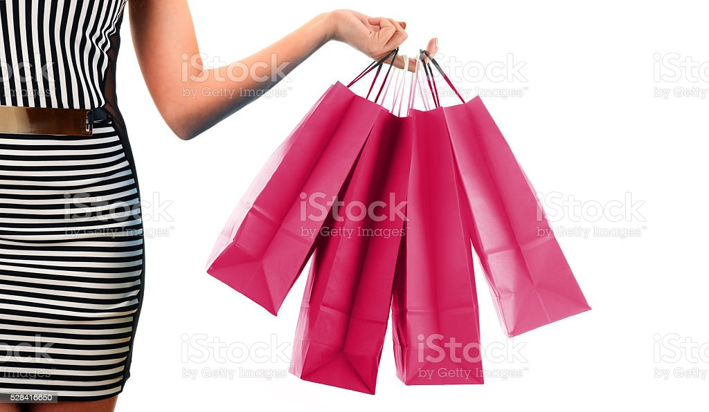 Woman's hand holding paper shopping bags isolated on white stock photo