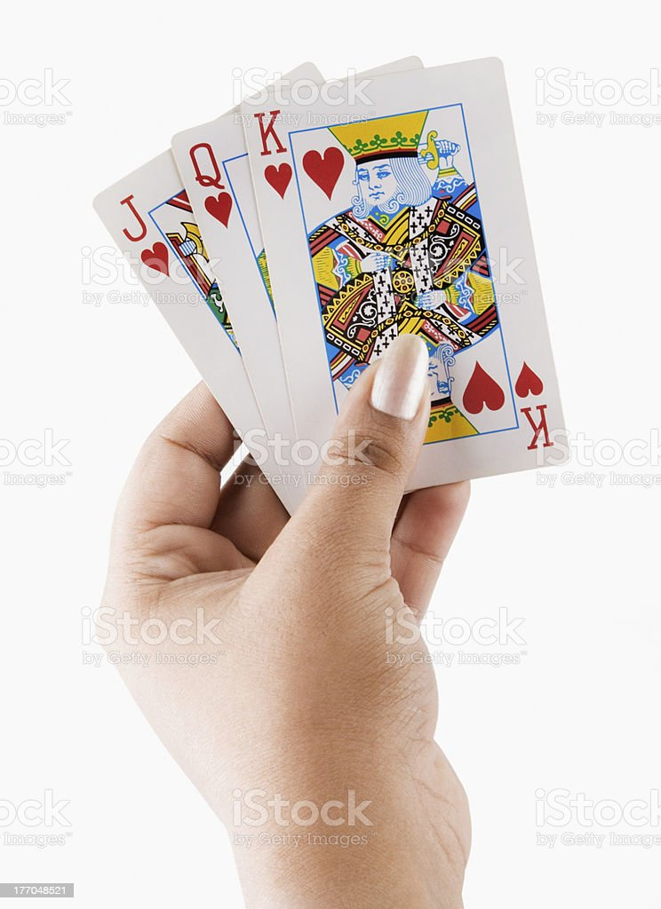 woman's hand holding playing cards stock photo