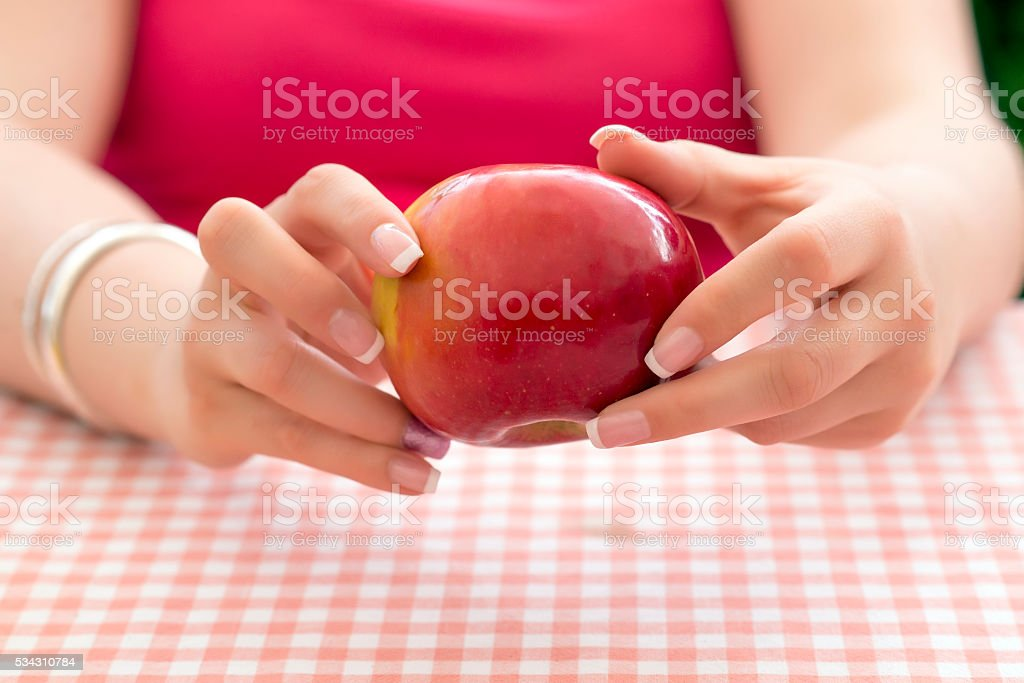 Woman's hand holding red apple stock photo