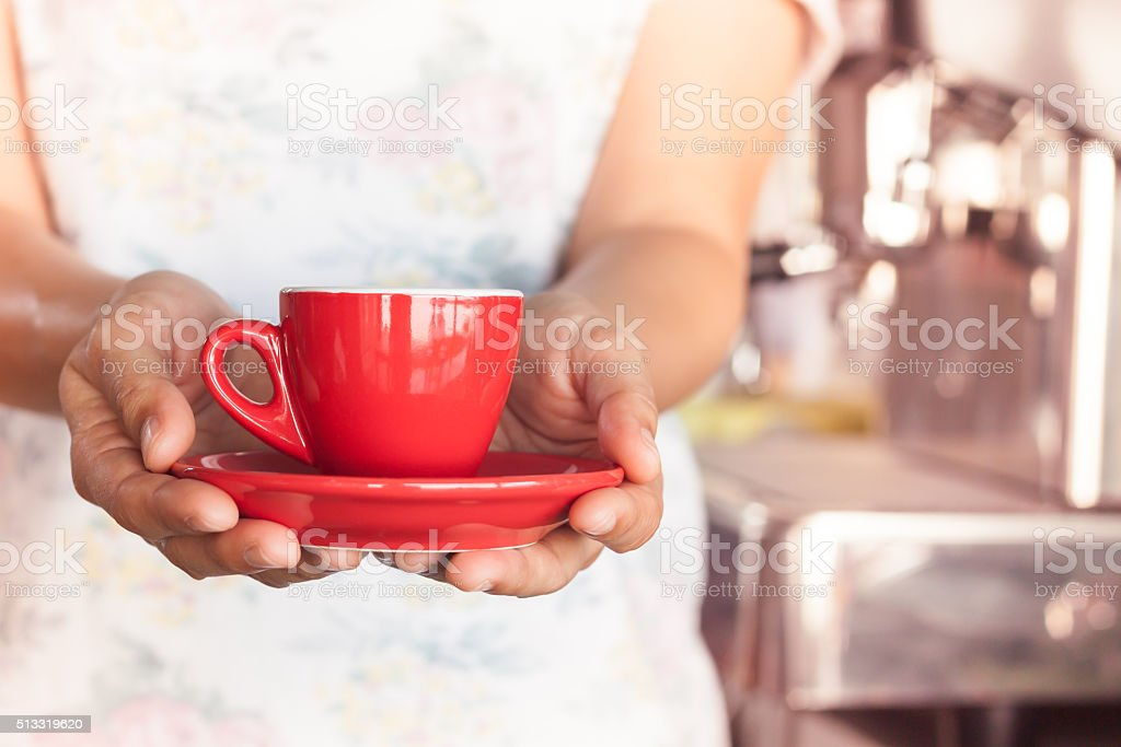 Woman's hand holding red coffee cup stock photo