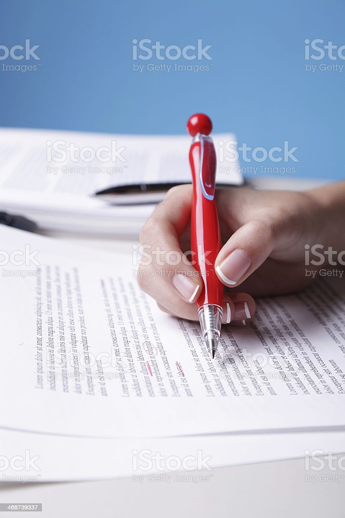 Woman's hand holding red pen proofreading a paper stock photo