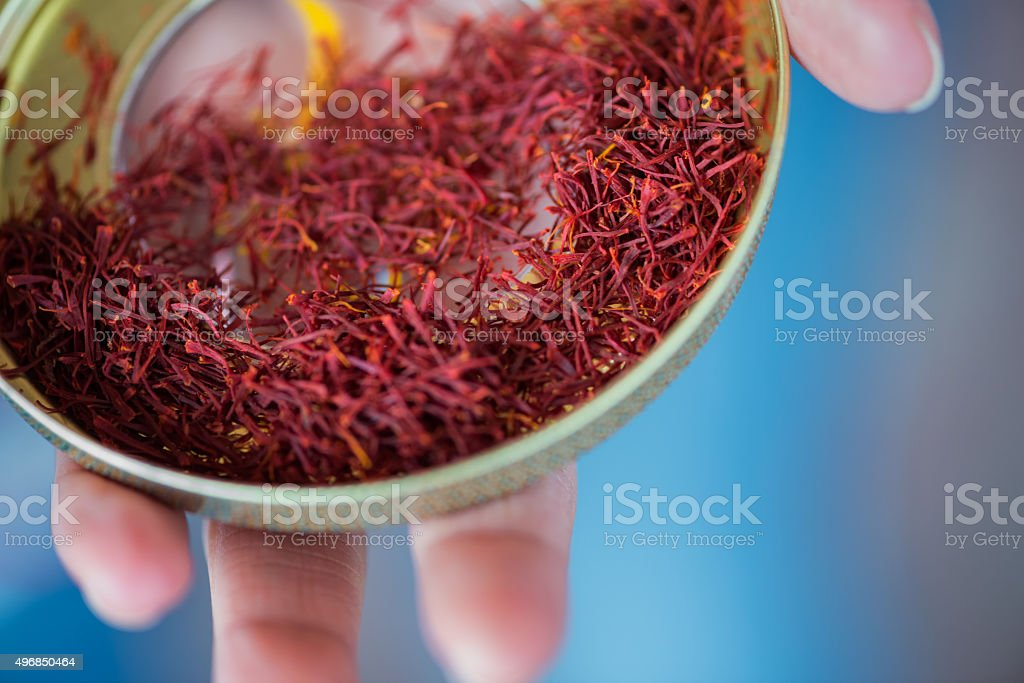 Woman's Hand Holding Red Saffron Spice from Dubai Souk, UAE stock photo