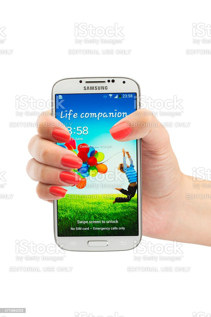 Woman's hand holding Samsung Galaxy S4,  isolated on white stock photo