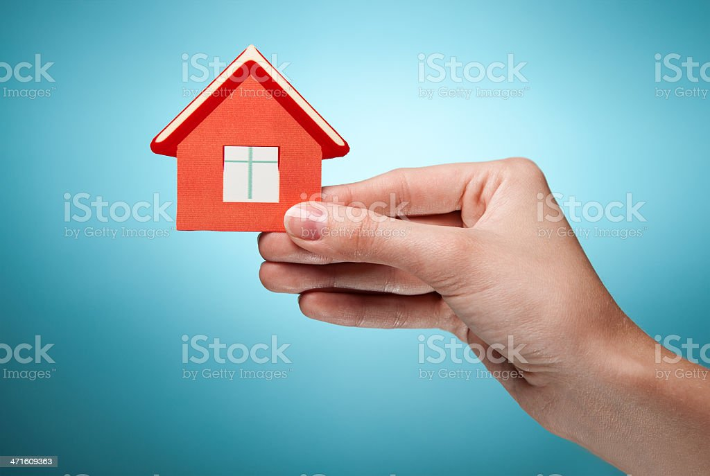 woman's hand holding sign of the house. Against blue background royalty-free stock photo