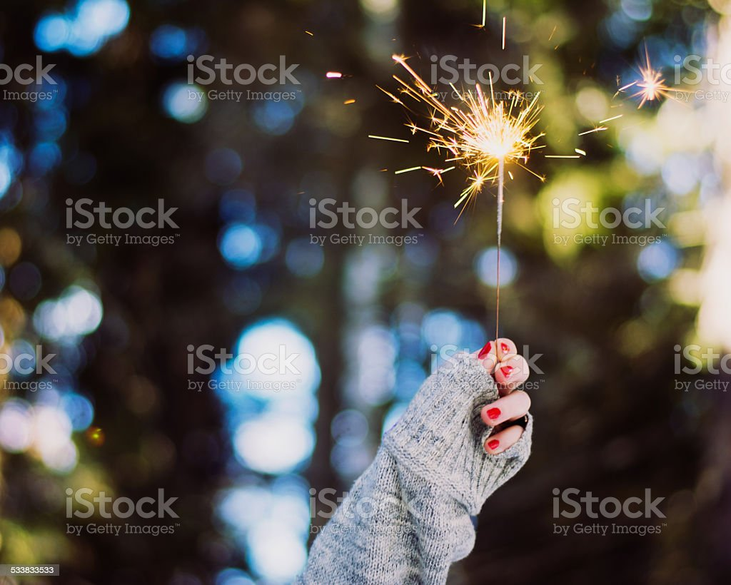 Woman's hand holding sparkler stock photo