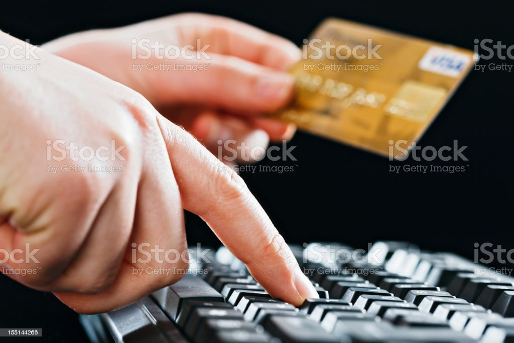 Woman's hand holds credit card and enters data on keyboard stock photo