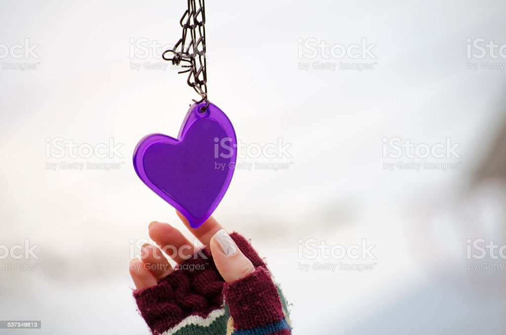 Woman's hand in mittens reaching for a heart royalty-free stock photo