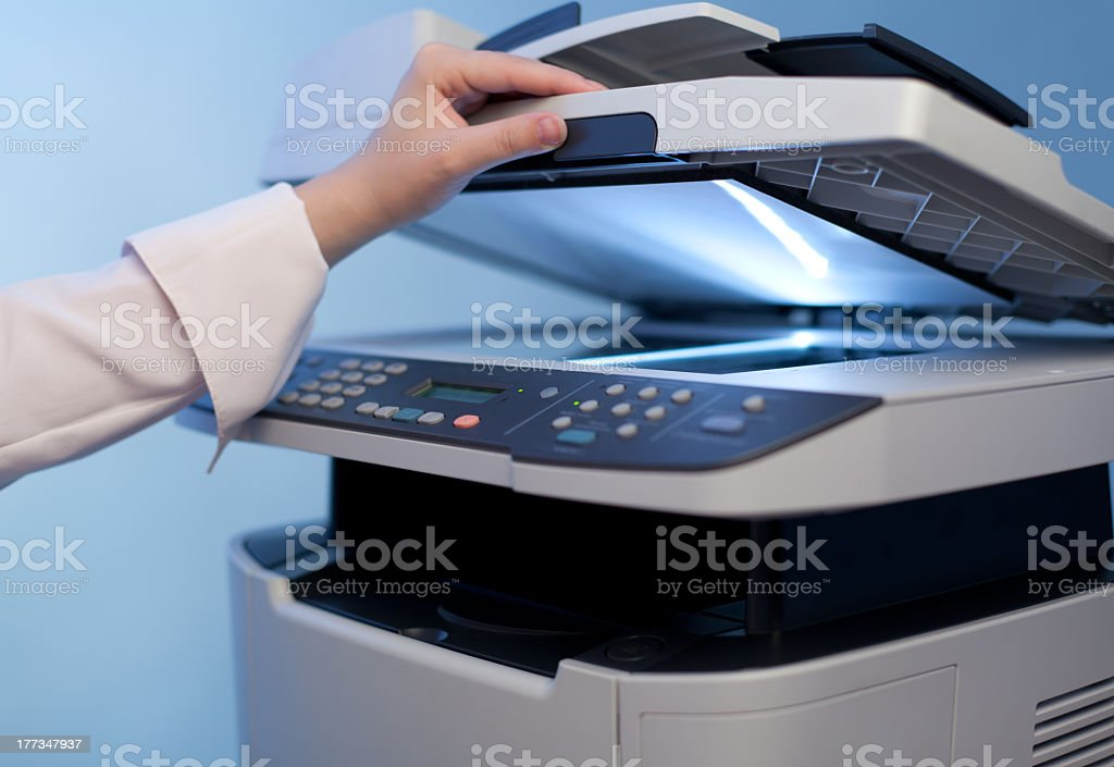 Woman's hand lifting lid of photocopier stock photo